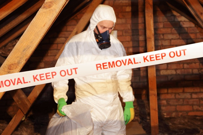 Man in hazard suit clearing meth-contaminated house.